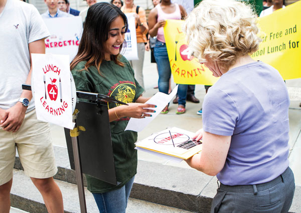 Two women at an event calling for free public school lunches.