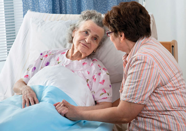 An elderly woman in a hospital bed and her visitor.