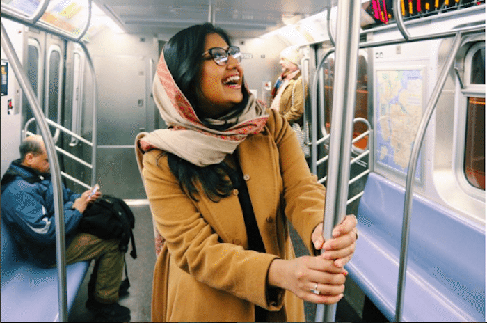 A Muslim young woman wearing a headscarf, glasses, and a long camel colored coat holding onto the pole on a subway car looking up.