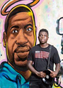 Babou Gaye in front of George Floyd mural